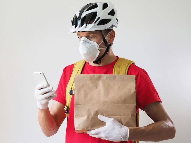 Mensajero ciclista con máscara protectora y guantes médicos entrega comida para llevar mirando el teléfono inteligente
