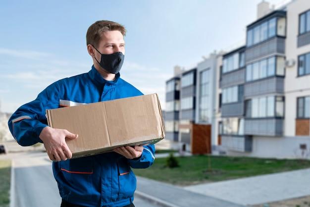 Un mensajero en la ciudad que lleva la caja de carga entrega el paquete.