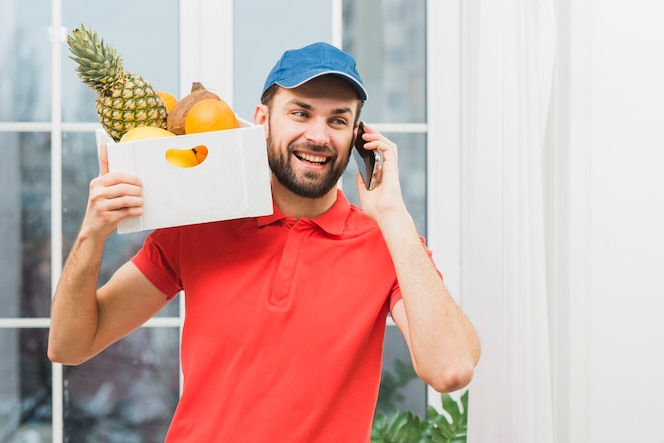 Mensajero con frutas hablando por teléfono