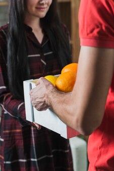 Mensajero de cultivo dando frutas al cliente
