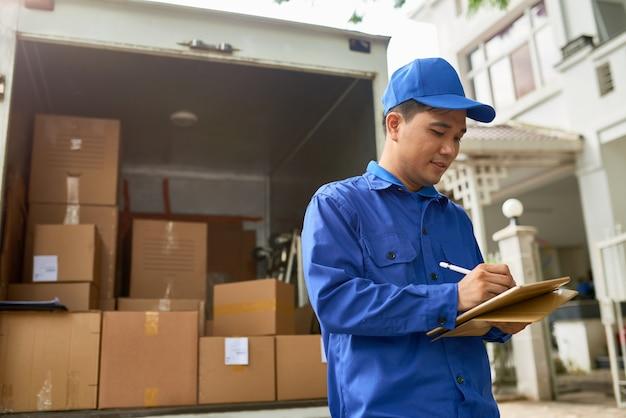 Mensajero de la empresa de mudanzas vietnamita de pie en el camión de reparto lleno de cajas y llenando la información en el contrato