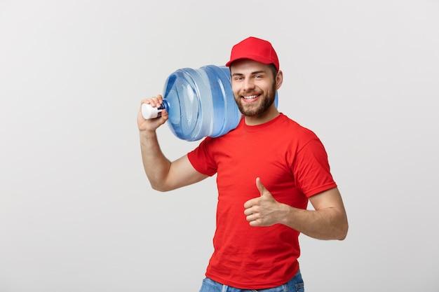 Mensajero de entrega de agua embotellada en camiseta roja y tapa que lleva el tanque de bebida y mostrando t
