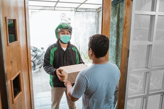 Mensajero de entrega con mascarilla mientras entrega el paquete