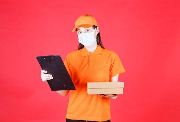 Mensajero femenino en código de vestimenta de color naranja y máscara sosteniendo una caja de cartón y leyendo el nombre y la dirección
