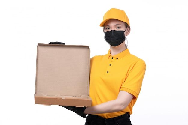 Un mensajero femenino joven de la vista frontal en guantes negros uniformes amarillos y máscara negra que sostiene la caja de la pizza