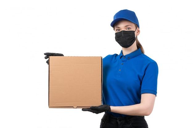 Un mensajero femenino joven de la vista frontal en guantes negros uniformes azules y máscara negra que sostiene el paquete de entrega de alimentos