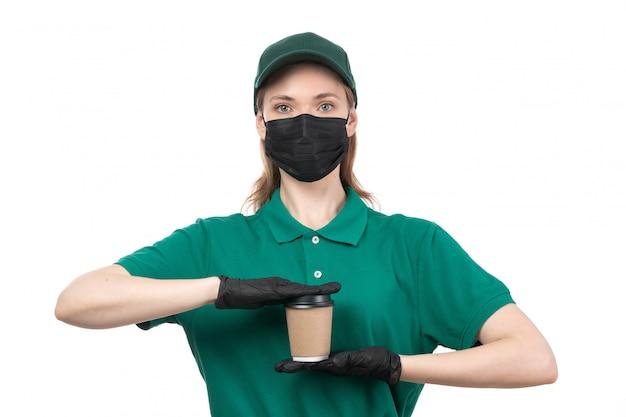 Un mensajero femenino joven de la vista frontal en guantes negros uniformes verdes y máscara negra que sostiene la taza de café