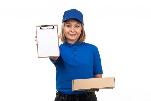 Un mensajero femenino joven de vista frontal en uniforme azul que sostiene el paquete de entrega de alimentos y el bloc de notas para firmas