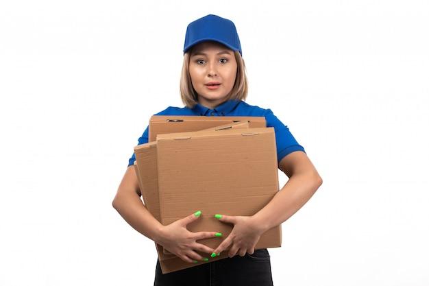 Un mensajero femenino joven de la vista frontal en uniforme azul que sostiene los paquetes de entrega de alimentos