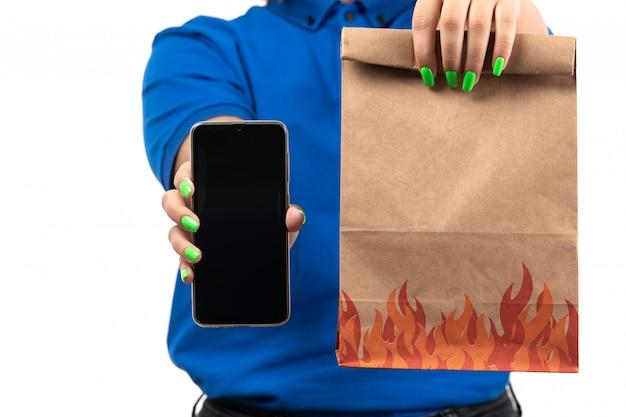 Un mensajero femenino joven de la vista frontal en uniforme azul que sostiene el teléfono y el paquete de entrega de alimentos
