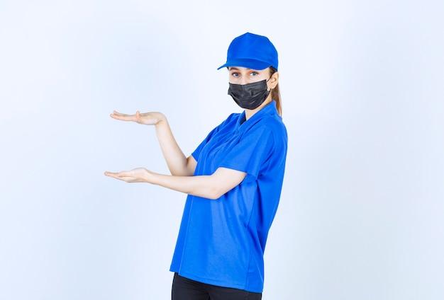 Mensajero femenino en máscara y uniforme azul que muestra la altura de un objeto