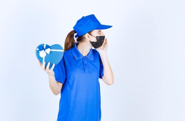 Mensajero femenino en máscara y uniforme azul sosteniendo una caja de regalo con forma de corazón y llamando a alguien para recibirlo