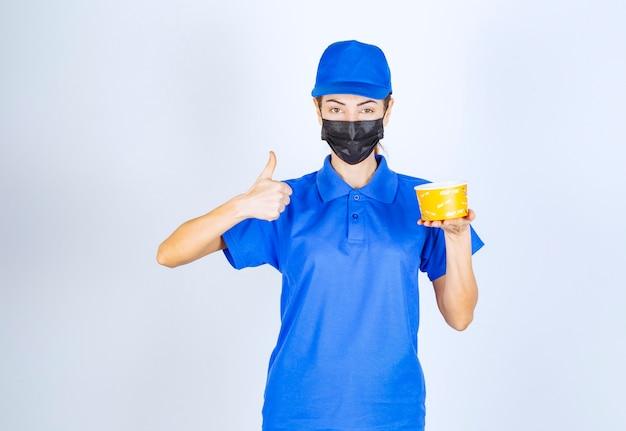 Mensajero femenino del restaurante en uniforme azul y mascarilla entregando comida para llevar y garantizando el buen gusto.