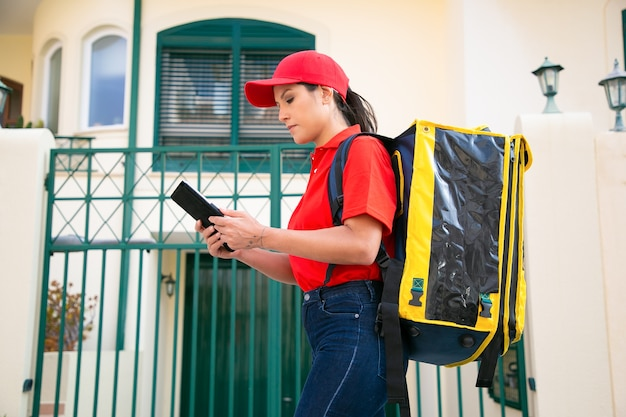 Mensajero femenino serio que mira la dirección en la tableta y que lleva la bolsa termo amarilla repartidora en la tapa roja que entrega el pedido expreso a pie. servicio de entrega de alimentos y concepto de compra online.