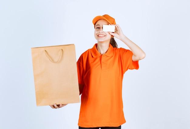 Mensajero femenino en uniforme amarillo entregando una bolsa de compras y presentando su tarjeta de visita