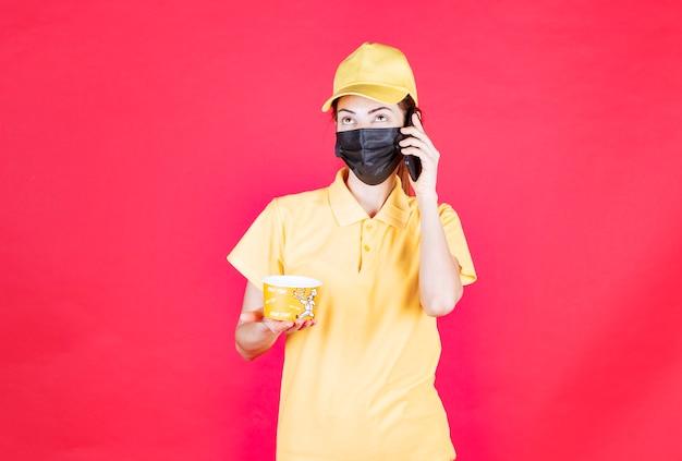Mensajero femenino en uniforme amarillo y máscara negra está entregando una taza de fideos mientras habla por teléfono