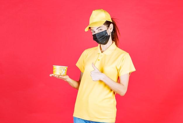 Mensajero femenino en uniforme amarillo y máscara negra está entregando una taza de fideos y mostrando el signo de la mano de disfrute
