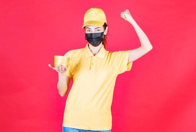 Mensajero femenino en uniforme amarillo y máscara negra está entregando una taza de fideos y mostrando su puño