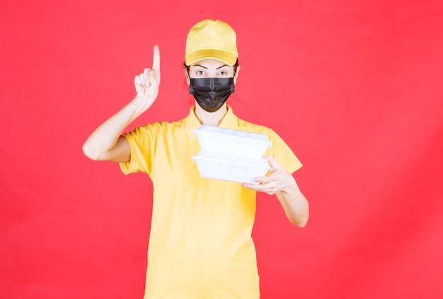 Mensajero femenino en uniforme amarillo y máscara negra sosteniendo múltiples paquetes de comida para llevar y teniendo una buena idea