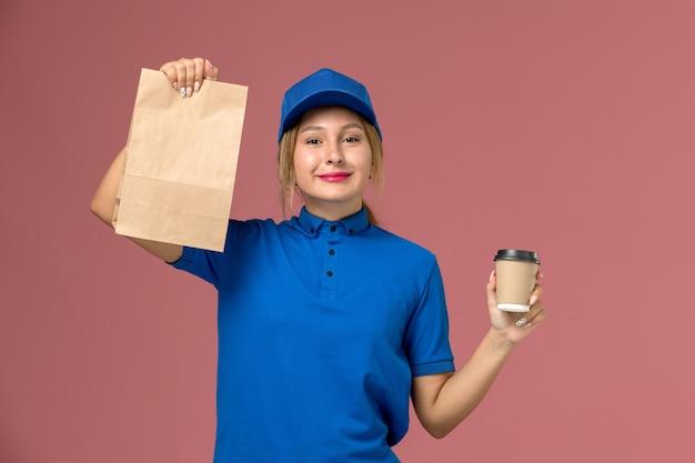 Mensajero femenino en uniforme azul posando sosteniendo una taza de café y paquete de comida sonriendo en rosa, servicio uniforme repartidor trabajadora