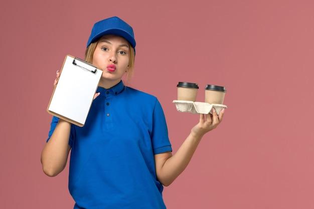 Mensajero femenino en uniforme azul sosteniendo tazas de café y bloc de notas pensando en rosa, trabajo de entrega uniforme del trabajador de servicio
