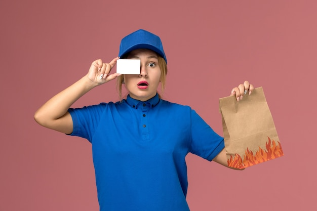 Mensajero femenino en uniforme azul con tarjeta de plástico blanco y paquete de comida en rosa claro, servicio de entrega uniforme