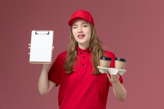 Mensajero femenino en uniforme rojo con bloc de notas y café en rosa, trabajador de entrega de servicio uniforme