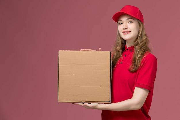 Mensajero femenino en uniforme rojo con caja de entrega de alimentos en rosa, trabajo de trabajador de entrega de servicio uniforme