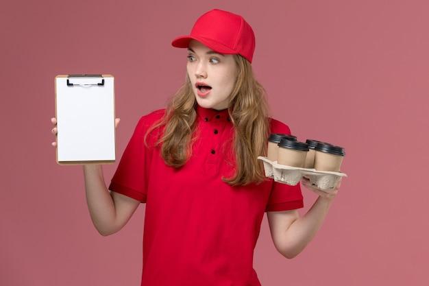 Mensajero femenino en uniforme rojo sosteniendo bloc de notas y tazas de café en rosa, trabajo de trabajador de entrega de servicio uniforme