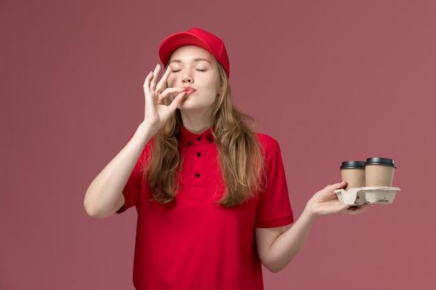 Mensajero femenino en uniforme rojo sosteniendo tazas de café de entrega en rosa claro, servicio uniforme de trabajo entrega del trabajador