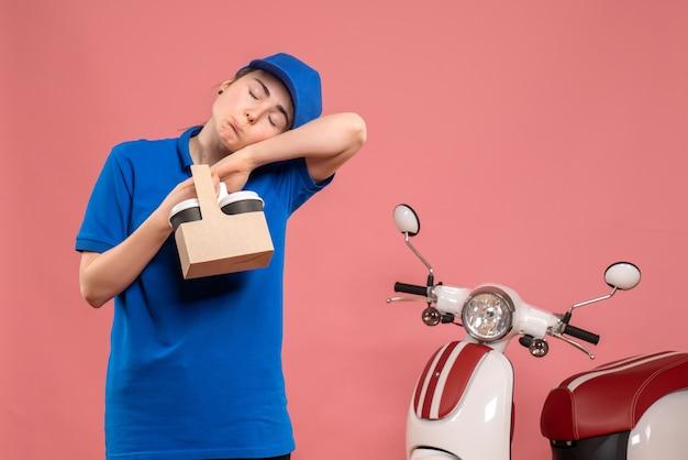 Mensajero femenino de vista frontal con café de entrega en bicicleta de mujer trabajadora de servicio uniforme de entrega de trabajo rosa