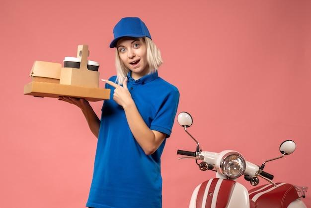 Mensajero femenino de vista frontal con caja de pizza y café en rosa