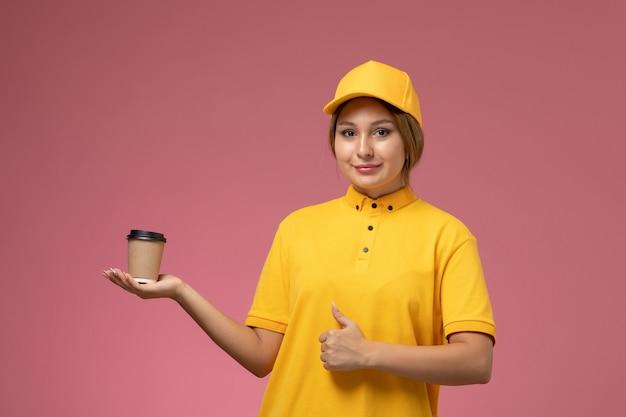 Mensajero femenino de vista frontal en capa amarilla uniforme amarillo sosteniendo una taza de café marrón de plástico con una sonrisa en el color femenino de entrega uniforme de escritorio rosa