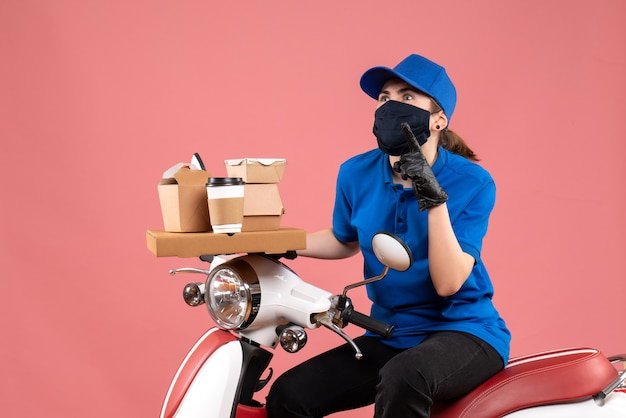 Mensajero femenino de vista frontal en máscara con entrega de alimentos en el rosa