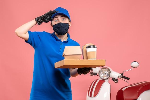 Mensajero femenino de vista frontal en máscara con entrega de café y comida en el rosa