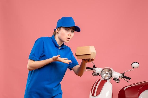Mensajero femenino de la vista frontal con el pequeño paquete de comida en la bicicleta rosada del servicio de entrega del trabajo del trabajador de la pizza de la mujer de la pizza