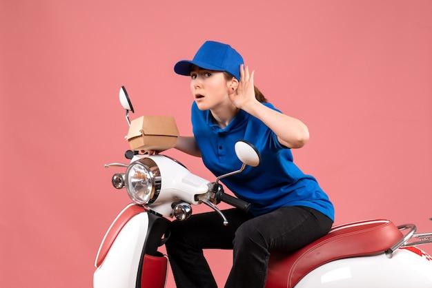 Mensajero femenino de la vista frontal que sostiene el pequeño paquete de comida en el rosa