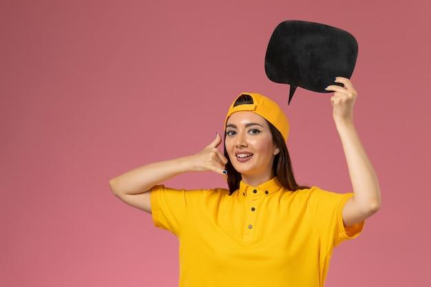Mensajero femenino de vista frontal en uniforme amarillo y capa con gran cartel negro en la entrega uniforme del servicio de trabajo de pared rosa