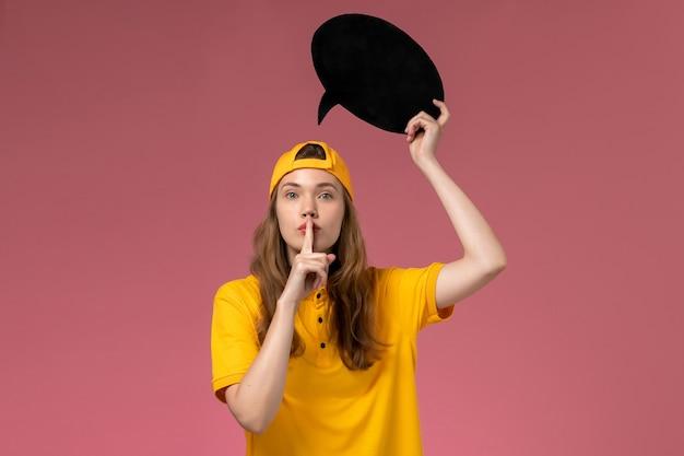 Mensajero femenino de vista frontal en uniforme amarillo y capa con gran cartel negro en la pared rosa, servicio de empresa trabajo uniforme de entrega