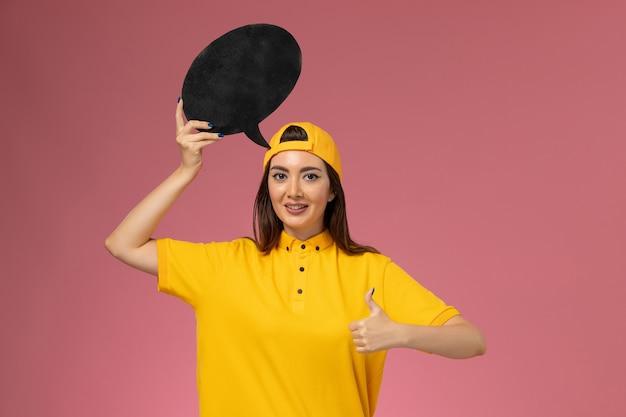 Mensajero femenino de vista frontal en uniforme amarillo y capa con gran cartel negro en la pared rosa, servicio de entrega uniforme