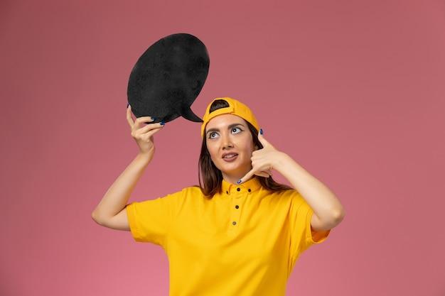Mensajero femenino de vista frontal en uniforme amarillo y capa con gran cartel negro en la pared rosa, trabajo de entrega uniforme de servicio