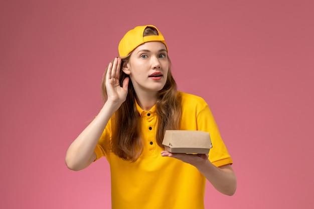 Mensajero femenino de vista frontal en uniforme amarillo y capa con paquete de comida de entrega en la pared rosa servicio de entrega uniforme trabajador de la empresa