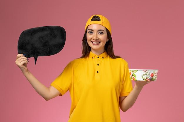 Mensajero femenino de vista frontal en uniforme amarillo y capa sosteniendo un cuenco de entrega redondo con letrero negro en el trabajo de entrega uniforme del servicio de pared rosa