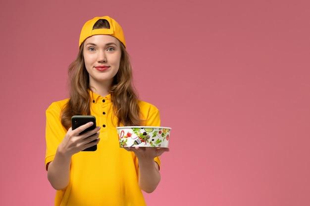 Mensajero femenino de vista frontal en uniforme amarillo y capa sosteniendo el cuenco de entrega y el teléfono en el trabajo uniforme de entrega de servicio de empresa de pared rosa