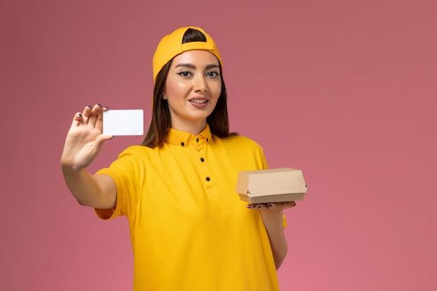 Mensajero femenino de vista frontal con uniforme amarillo y capa sosteniendo un pequeño paquete de comida de entrega y una tarjeta en la empresa de entrega uniforme de trabajo de trabajo de servicio de pared rosa claro