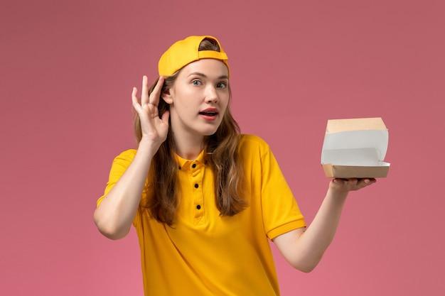 Mensajero femenino de vista frontal con uniforme amarillo y capa sosteniendo un pequeño paquete de comida de entrega vacío tratando de escuchar en el uniforme de entrega de servicio de pared rosa claro