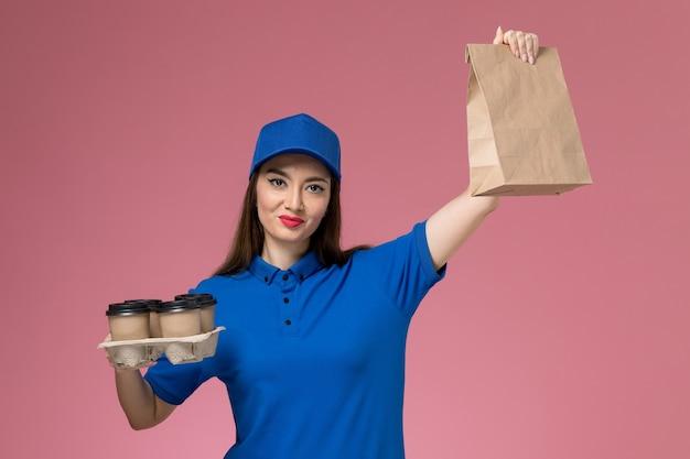 Mensajero femenino de la vista frontal en uniforme azul y capa que sostiene el paquete de comida de las tazas de café en la pared rosada