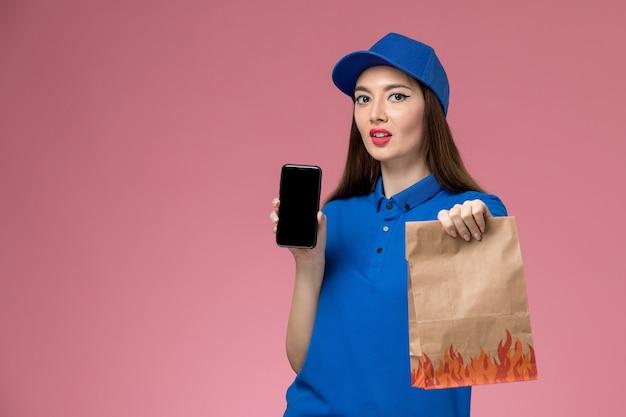 Mensajero femenino de vista frontal en uniforme azul y capa sosteniendo su teléfono y paquete de comida de papel en la pared rosa