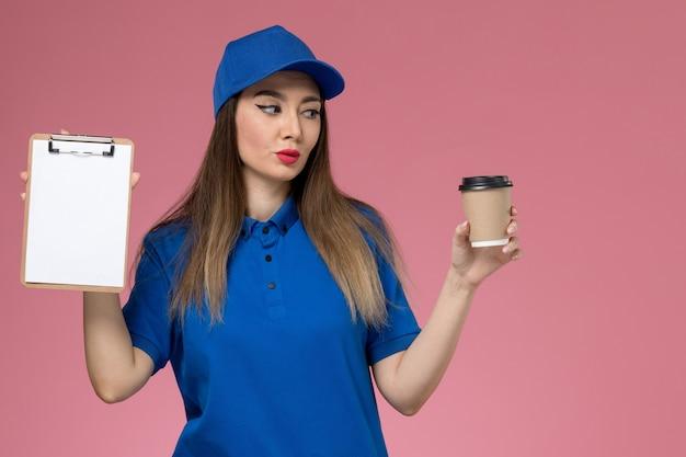Mensajero femenino de vista frontal en uniforme azul y capa sosteniendo la taza de café de entrega y el bloc de notas en el trabajador de la pared rosa