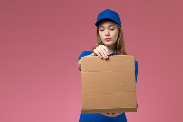 Mensajero femenino de vista frontal en uniforme azul sosteniendo la caja de entrega de alimentos y abriéndola sobre fondo rosa empresa uniforme de servicio de trabajo